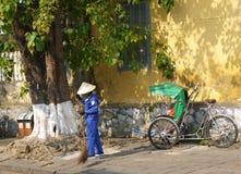 Straßenkehrmaschinearbeitskraft mit einem Besen, der die Straße in Hoi An säubert lizenzfreie stockfotos