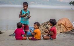 Straßenkinderspiel mit Lehm von der der Ganges-Bank bei Mallick Ghat, Blumenmarkt, Kolkata, Indien Stockfotografie