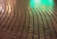 Straßenkopfstein in der Nacht, die im Grün funkelt Lizenzfreie Stockfotos