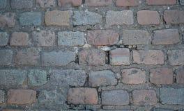 Straßenkopfsteine in den Grau- und Lichtrottönen Stockfotos
