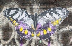 Straßenkunst in London: Grafik, die einen großen Schmetterling auf einer Backsteinmauer darstellt Stockfotografie