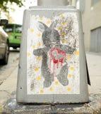 Straßenkunsthäschen mit einem roten Bratenfettherzen auf der Basis eines Bürgersteigslaternenpfahls Lizenzfreies Stockfoto