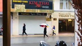 Straßenland, Leute, die am regnerischen Tag an DA-Lat, Vietnam aufwecken stockfotografie