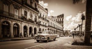 Straßenlandschaft auf der Hauptstraße mit amerikanischen Weinleseautos des Antriebs in Havana Cuba - Retro- Serie-SEPIA Kuba-Repo Stockfotos