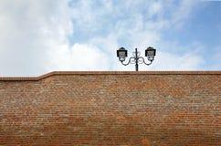 Straßenlaterne auf die Oberseite einer Backsteinmauer Stockfotografie