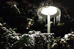 Straßenlaterne nachts umfasst mit Schnee und Eiszapfen stockbilder