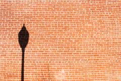 Straßenlaterne-Schattenbild auf gebrochener Backsteinmauer stockfoto