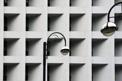 Straßenlaternen gegen modernes abstraktes städtisches Gebäude Ausführliches geometrisches Schwarzweiss-Muster in der Stadt Lizenzfreie Stockbilder