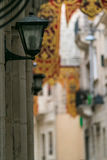 Straßenlaternenpfahl mit Dekorationen eines Straßenfestes im Hintergrund Lizenzfreie Stockfotos
