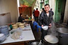 Straßenlebensmittel, Bürgersteigssnack, Koch bereitet die Straße, chinesische Teller vor Lizenzfreies Stockfoto