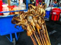 Straßenlebensmittel Gegrillte Krakenaufsteckspindel mit Nahrungsmittelwagen in Thailand lizenzfreie stockfotografie