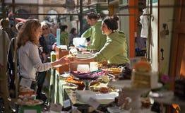 Straßenlebensmittelverkäufer, der Lebensmittel zu Frauen führt Lizenzfreies Stockfoto