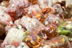 Straßenlebensmittelwarenkorb mit exotischem asiatischem Mitnehmerlebensmittel in den Plastiktaschen Lizenzfreie Stockfotos