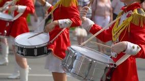 Straßenleistung des festlichen Marsches der Schlagzeugermädchen in den roten Kostümen auf Stadtstraße stock footage