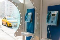 Straßenmünztelefon mit gelbem Taxi im Hintergrund Reisekonzept, Passagiertransport, Kommunikation 3d übertragen Bild Lizenzfreies Stockbild