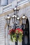 Straßenmetallweinlese Lampe mit dem Hängen der roten Pelargonie blüht Stockfoto