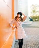 Straßenmode, hübsches Frauenmodell im Mantel und Hut lizenzfreie stockfotos
