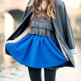 Straßenmodeblick mit blauem Rock, Jacke, Kleid und schwarzen Strumpfhosen Stockbild