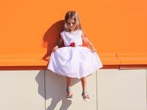 Straßenmodekind, kleines Mädchen im Kleid nahe bunter Wand Lizenzfreies Stockfoto