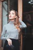 Straßenmodekonzept: Porträt der eleganten jungen Schönheit, die nahe der Tür aufwirft Taille oben Junge Frau der Schönheit auf st Lizenzfreies Stockbild