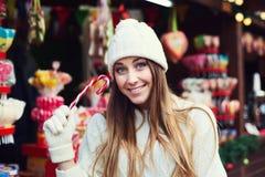 Straßenmodeporträt der lächelnden schönen jungen Frau, die Zuckerstangen hält und Kamera betrachtet Tragender Klassiker Dame Stockbilder