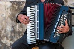 Straßenmusiker, der ein Akkordeon spielt Stockbild