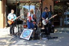 Straßenmusiker, die für die Leute vorbei überschreiten, im Stadtzentrum gelegenes Saratoga Springs, New York, 2016 spielen Lizenzfreie Stockfotos