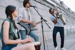 Straßenmusiker versehen die Ausführung mit Gitarrentrommel und -Saxophon auf sonnigem mit einem Band stockfotografie