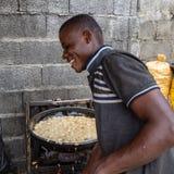Straßennahrungsmittel in Lagos Nigeria; glücklicher Verkäufer, der Akara entlang der Straße brät stockfotografie