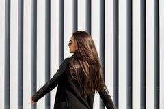 Straßenporträt des erstaunlichen jungen Modells, das modernen Mantel trägt, Stockfoto