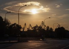 Straßenrandlaternen und Hafenkräne gegen den Hintergrund eines Sonnenuntergangs mit schönen Wolken in Klaipeda, Litauen lizenzfreies stockfoto