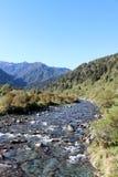 Straßenrandstromlandschaft, Berge hinten, NZ Stockbild