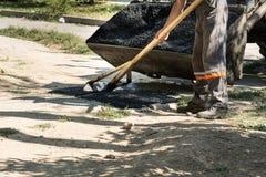 Straßenreparaturdetails, Arbeitskraft planiert den heißen Asphalt stockfoto