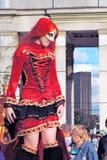 Straßenschauspieler-Rothaarigefrau wirft für Fotos im roten Kleid auf Lizenzfreie Stockfotografie