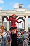 Straßenschauspielerfrau wirft für Fotos im roten Kleid auf Stockbilder