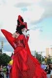 Straßenschauspielerfrau wirft für Fotos im roten Kleid auf Stockfoto