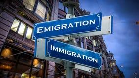 Straßenschild-Auswanderung gegen Immigration stockbilder