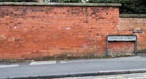 Straßenschild gegen Backsteinmauer Stockbilder