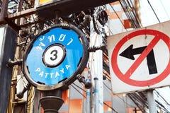Straßenschild PATTAYA 3 in englischem und in thailändischem nahe bei einer KEINER LINKSKURVE Stockbild