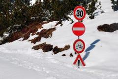 Straßenschilder umfaßt von Snow Stockfotografie