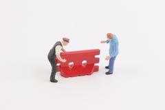 Straßensperrenhintergrund mit Miniarbeitskraft Lizenzfreies Stockfoto