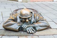 Straßenstatue des Mannes bei der Arbeit in Bratislava nannte Cumil, Slowakei Stockbild