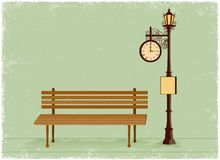 Straßenuhr und -Laternenpfahl mit Parkbank Lizenzfreie Stockbilder