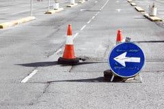Straßenumwegzeichen und passendes Schlagloch der Kegel Stockfotografie