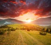 Straßenwanderweg in den bunten Bergen des Herbstes auf Hintergrund des Tales und des ausgezeichneten Sonnenunterganghimmels stockfotos