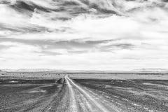 Straße in geschlagenem Teil der Dürre des Tankwa-Karoo einfarbig stockfotos
