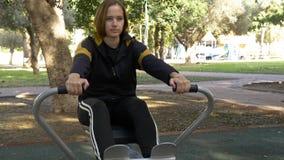 Straßensimulator des Rudersports, Frau, die sonnigen Tag ausbildet lizenzfreie stockbilder