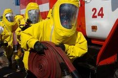 Strażacy w ochronnych kostiumach, maskach gazowych i wężu elastycznym, dostają gotowymi dla pracy obrazy royalty free