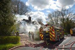 Strażacy brać się do ogienia w wiejskiej chałupie Fotografia Stock