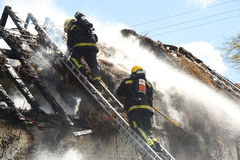 Strażacy brać się do poszycie dachu ogienia Zdjęcia Stock